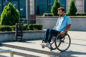 Fotografie handsome man in sunglasses using wheelchair on street looking at stairs without ramp