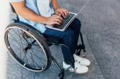 oříznutý obraz člověka na vozíku pomocí přenosného počítače na ulici