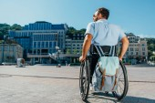 Fotografie back view of man using wheelchair with bag on street