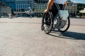 Fotografie Bild des Menschen mit Rollstuhl mit Tasche in Stadt beschnitten