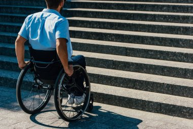 back view of disabled man using wheelchair on street and stopping near stairs without ramp