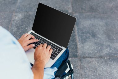 Cropped image of man in wheelchair using laptop with blank screen on street stock vector