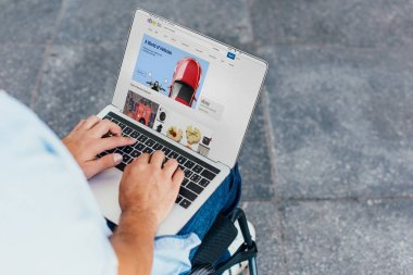cropped image of man in wheelchair using laptop shopping online with ebay website on street