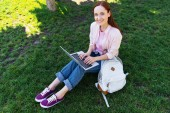 high angle view of smiling attractive freelancer using laptop in park and looking at camera