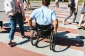 back view of boyfriend in wheelchair and girlfriend crossing crosswalk in city
