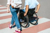 Fotografie cropped image of disabled boyfriend in wheelchair and girlfriend crossing crosswalk in city