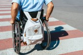 Fotografie cropped image of disabled man in wheelchair with bag riding on crosswalk