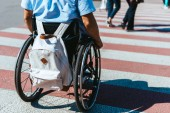 cropped image of man in wheelchair with bag riding on crosswalk