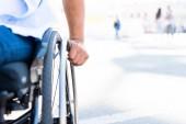 oříznutý obraz postižený člověk používající invalidní vozík na ulici