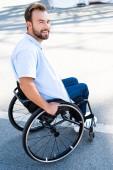 pohledný usmívající se muž používající invalidní vozík na ulici a při pohledu na fotoaparát