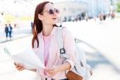 vzrušený turisticky v sluneční brýle drží mapu na ulici a hledat dál