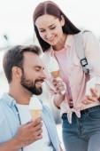 Fotografie portrét z přítelkyně se zmrzlinou ukazuje něco na smartphone do kluka na vozíku na ulici