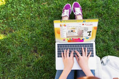 cropped image of woman using laptop with loaded aliexpress page in park