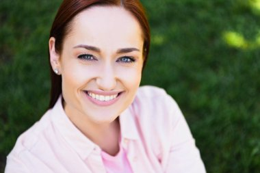 head and shoulders of attractive happy redhair woman in pink shirt looking at camera in park