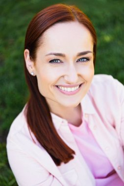 high angle view of attractive smiling redhair woman in pink shirt looking at camera in park
