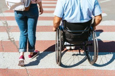 cropped image of boyfriend in wheelchair and girlfriend crossing crosswalk in city