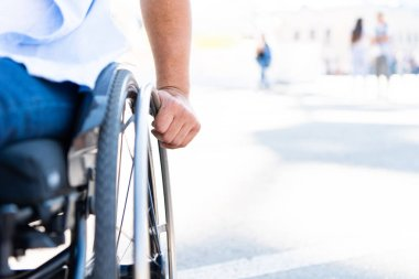 cropped image of disabled man using wheelchair on street