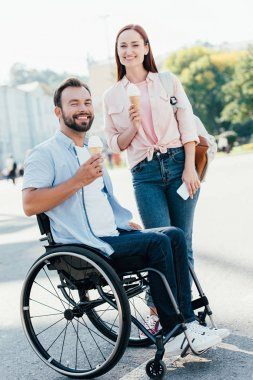 Smiling handsome boyfriend in wheelchair and girlfriend with ice cream looking at camera on street stock vector