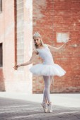 Fotografie attractive young ballerina in white tutu and pointe shoes dancing on street