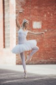 attractive young ballerina in white tutu and pointe shoes dancing on street