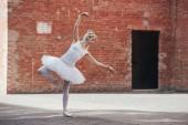 Fotografie po celé délce pohled elegantní mladé tanečnice tančí na ulici