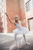 krásné elegantní mladá baletka v bílém tutu tančí na ulici