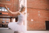 attractive young ballerina in white tutu dancing on street