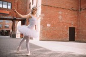 Fotografia bello giovane ballerino di balletto in tutu e pointe scarpe sulla strada