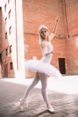 Fotografie attractive ballerina in white tutu and pointe shoes dancing and looking away on street