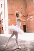 attractive ballerina in white tutu and pointe shoes dancing on street