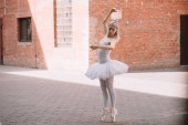 Fotografie young ballerina in white tutu and pointe shoes dancing on street