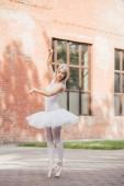 Fotografie krásná mladá baletka v pointe boty tance na městské ulici