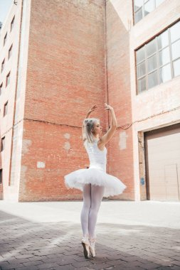 back view of young ballerina dancing on urban city street
