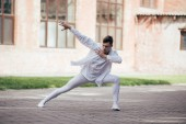 Fotografie handsome young man dancer in white clothes dancing on urban city street