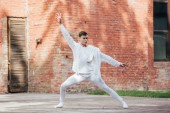 Fotografie handsome young man in white clothes dancing on urban street