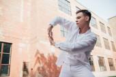 nízký úhel pohledu mladého muže v bílých šatech tančí na ulici