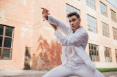 young male dancer in white clothes dancing on city street