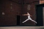 mladá baletka v skok na městské ulici