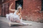 krásná mladá baletka při tanci na ulici při pohledu na fotoaparát
