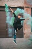 mladý samec moderní tanečnice skákání do zeleného dýmu městských ulic