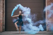 Fotografie girl dancing in blue smoke and looking at camera on urban city street