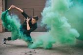 pohledný mladý samec tanečnice v zelené kouře na ulici