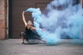 Fotografie mladá moderní tanečnice tančí v modrém kouře na ulici