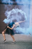 Fotografie side view of young female dancer dancing in blue smoke on street