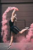 Fotografie side view of young female dancer dancing in pink smoke on street