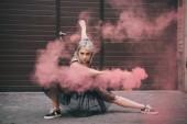 schönes Mädchen, das in rosa Rauch tanzt und auf der Straße in die Kamera schaut