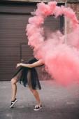 flexibilní mladé ženy tančí v růžové kouře na městské ulici