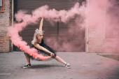 Photo young woman dancing in pink smoke on urban street