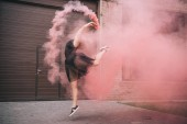 Fotografie attractive young woman dancing in pink smoke on street
