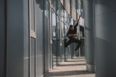 Fotografie full length view of young man in black clothes jumping in dance